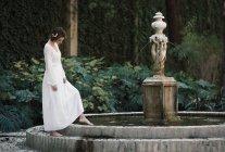 Femme brune posant à fontaine dans le parc — Photo de stock