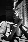 Mujer joven sentada en el balcón a la luz del sol - foto de stock