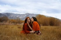 Young girls in affection sitting on dry grass with mountains on background. — Stock Photo