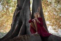 Offres femme en robe, assis sur des racines d'arbre énorme — Photo de stock
