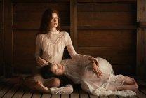 Giovani ragazze che indossano abiti eleganti vecchio stile e posingin tenero abbraccio su legno . — Foto stock