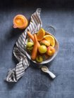 Nature morte de fruits et légumes orange sur un bol sur une table bleue minable . — Photo de stock