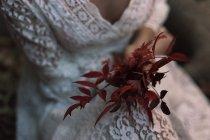 Sección media de la mujer en vestido de encaje blanco y la celebración de follaje rojo . - foto de stock