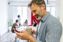 Людина перегляду смартфон в офісі — стокове фото