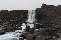 Acqua che cade dalla scogliera rocciosa — Foto stock