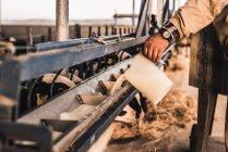 Farmer pouring milk to feeding machine — Stock Photo