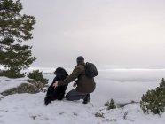 Турист і собака у snowy гори — стокове фото