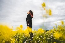 Woman standing on lawn with yellow flowers — Stock Photo
