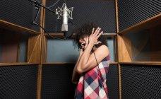 Woman singing in studio — Stock Photo