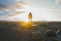 Woman standing on wooden table at sunset — Stock Photo