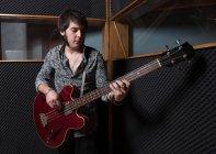 Man playing guitar in studio — Stock Photo