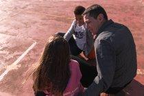 Отец и дети, сидя на баскетбол — стоковое фото