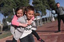 Boy carrying sister on piggyback — Foto stock
