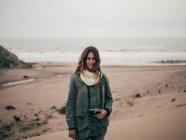Mujer de pie en la costa del océano - foto de stock