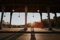 Ліхтарі і стовпців на вулиці з людьми, проходячи на фоні на заході сонця — стокове фото