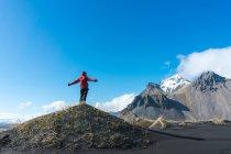 Uomo in piedi sulla collina e guardando le montagne — Foto stock