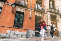 Смеющиеся женщины, идущие по городу — стоковое фото