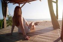 Woman sitting on sandy beach — Stock Photo