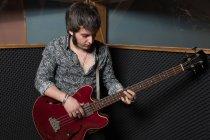 Uomo che suona la chitarra in studio — Foto stock