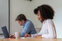 Donna seduta in ufficio e scrittura in taccuino — Foto stock