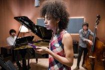 Проверка смартфон певица во время репетиции — стоковое фото