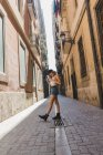 Funky woman walking on paved street — Stock Photo