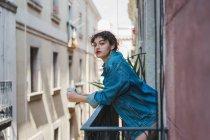 Жінка в джинсового куртці стоячи на балконі — стокове фото