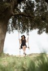 Mädchen sitzen auf der Schaukel unter Baum — Stockfoto
