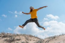 Man jumping on sandy hill — Stock Photo