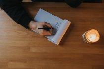 Feminino mão escrevendo no bloco de notas — Fotografia de Stock