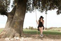 Girl with smartphone sitting on swings — Stock Photo