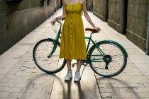 Жінка, стоячи на вулиці з велосипеда — стокове фото