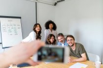 Hands taking photo of business team — Stock Photo