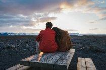 Casal que estava na mesa de madeira, ao pôr do sol — Fotografia de Stock