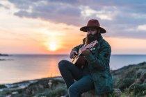 Uomo seduto con la chitarra sulla costa — Foto stock