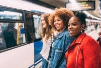 Молодые многорасовые женщины ждут поезда — стоковое фото