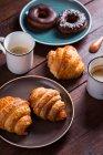 Чашки кави і свіжі круасани з пампушками — стокове фото