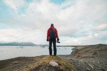 Homem de pé no lago com câmera — Fotografia de Stock