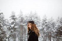 Mujer de pie en el camino cubierto de nieve - foto de stock