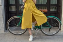 Femme debout avec vélo vintage — Photo de stock