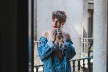 Жінка в джинсового куртці тримає Кубок на балконі — стокове фото
