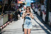 Женщина с камеры стоя на улице — стоковое фото