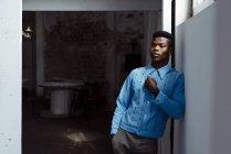 Стильный черный человек, опираясь на стене — стоковое фото