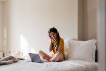 Donna in cuffia con computer portatile — Foto stock