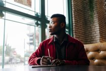 Black man sitting in cafe and writing — Stock Photo