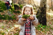 Girl holding moss in forest — Stock Photo