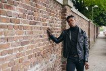 Чорна людина, спираючись на цегляна стіна — стокове фото