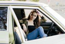 Femme assise dans une voiture vintage — Photo de stock
