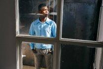 Homem olhando para fora janela suja — Fotografia de Stock