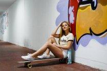 Chica rubia sentada en longboard - foto de stock